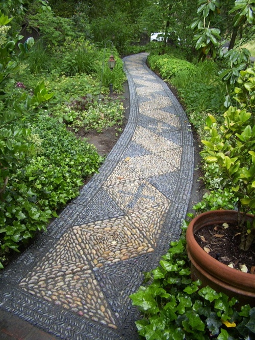 a grey and neutral pebble gardne path with a geometric pattern is a stylish idea that will add a modern feel to the outdoor space
