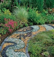 a colorful pebble garden path with mint green, rust, grey and black pebbles and catchy patterns