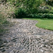 a black pebble garden path that contrasts the manicured lawn next to it and creates a bold and catchy look