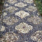 a black and neutral pebble garden path with a floral pattern and lining will give a vitnage feel to your outdoor space