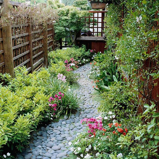 a small and tight pathway of grey pebbles with catchy and textural greenery next to it looks very cool and natural