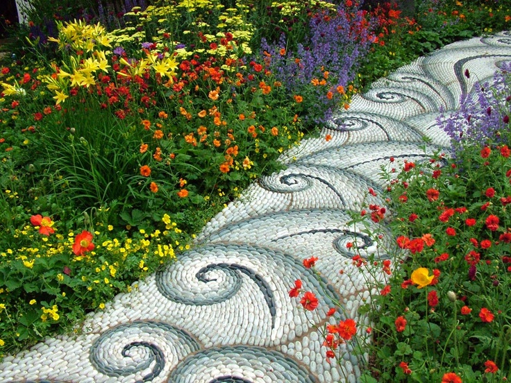 a white, grey and ombre green pebble path with an eye catchy pattern is a bold idea for a bright garden