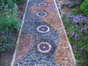 a green, burgundy, rust and grey pebble pathway with several patterns and neutral lining up is a very bold idea with a boho feel