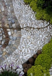 a catchy pebble path in several colors and with daisies made of pebbles looks super cute and rustic