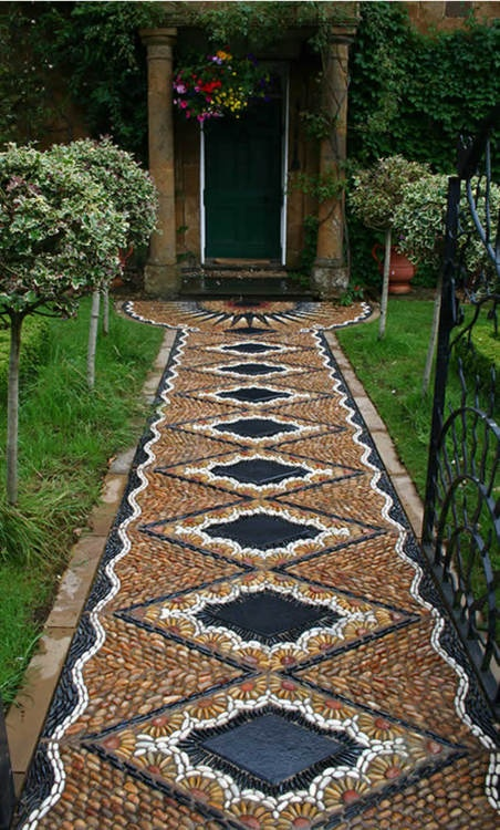 a super bold and unique pebble garden path with a geometric and floral pattern in yellow, white and black