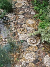 an earthy tone pebble path that imitates amonites is a great idea to go for next to a water feature like a pond here