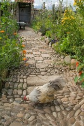 a garden path made of pebbles and tiles mixed up is a relaxed and fresh idea with a rustic feel