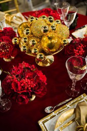 a refined deep red and gold Christmas tablescape with an ornament centerpiece and red blooms plus gold chargers and cutlery