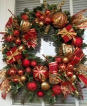 a chic and refined Christmas wreath of red and gold ornaments and ribbons and evergreens is a cool idea
