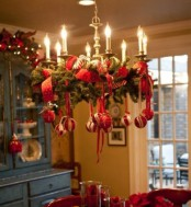 a Christmas chandelier of evergreens, red and white ornaments on red ribbons and gold candleholders