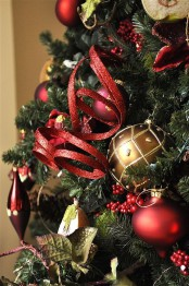 a Christmas tree decorated with red and gold ornaments, berries, foliage, glitter ribbons