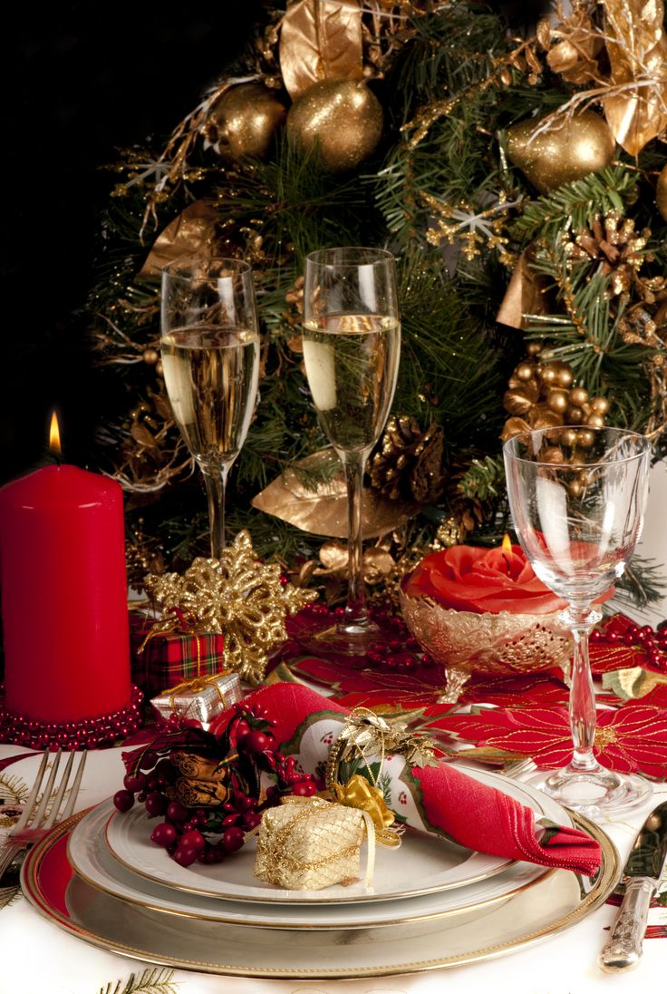 gold and red Christmas styling with candles, gilded chargers and cutlery, placemats and a tree decorated with gold ornaments
