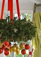 a gorgeous Christmas chandelier of evergreens, gold and red ornaments and red ribbons is amazing for holiday decor