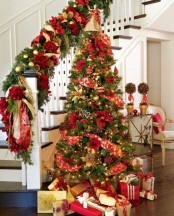 traditional gold and red Christmas decor – a Christmas tree with such decor and lights and railing decorated with evergreens, gold and red plus pinecones