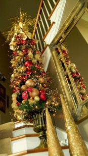 a red and gold Christmas mini tree composed of ornaments and bows is a shiny festive decoration