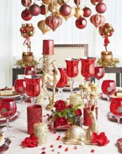 red and gold glitter Christmas decor with ornaments hanging over the table, red glasss and gold candles and much more for the holidays