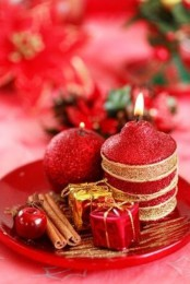 red and gold candles on a plate and mini gift boxes for decor plus cinnamon sticks