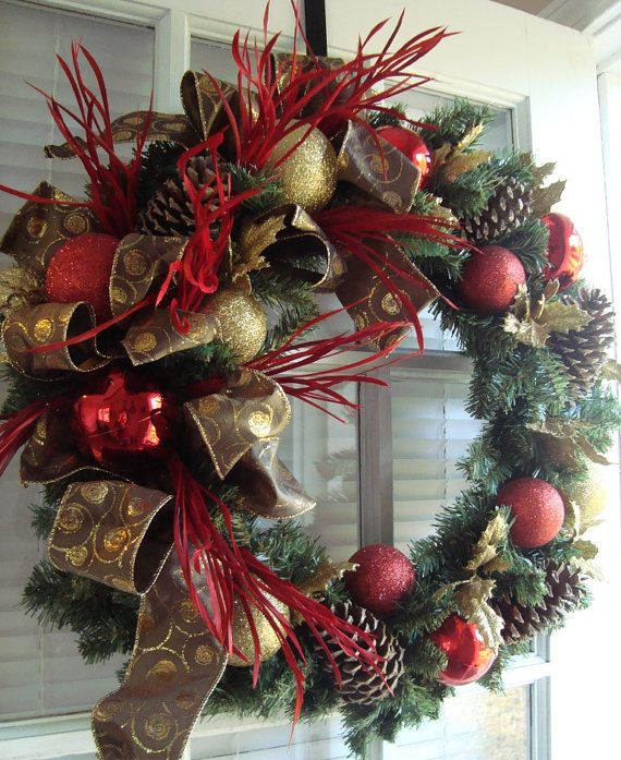 a lush evergreen Christmas wreath with gold and red glitter ornaments, bows and ribbons plus branches