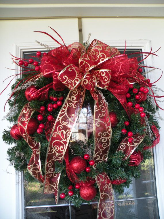 an evergreen wreath with red ornaments of various sizes and red and red and gold ribbons and bows