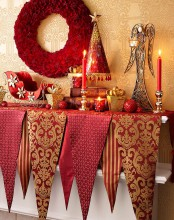 a refined red and gold Christmas table with table runners, candles, a rhinestone Christmas tree
