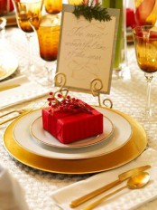 an elegant gold and red Christmas table with gold chargers and cutlery, amber glasses and evergreens