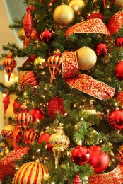 a Christmas tree decorated in red and gold ornaments, with lights, ribbons and lots of glitter