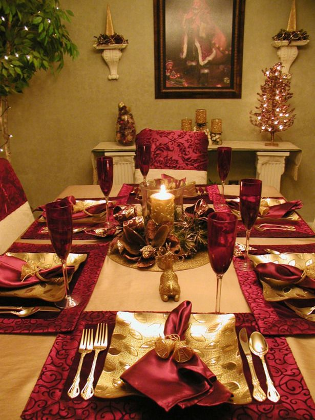a traditional and glam red and gold Christmas table setting with napkins, gold chargers and cutlery and a bow and candle centerpiece
