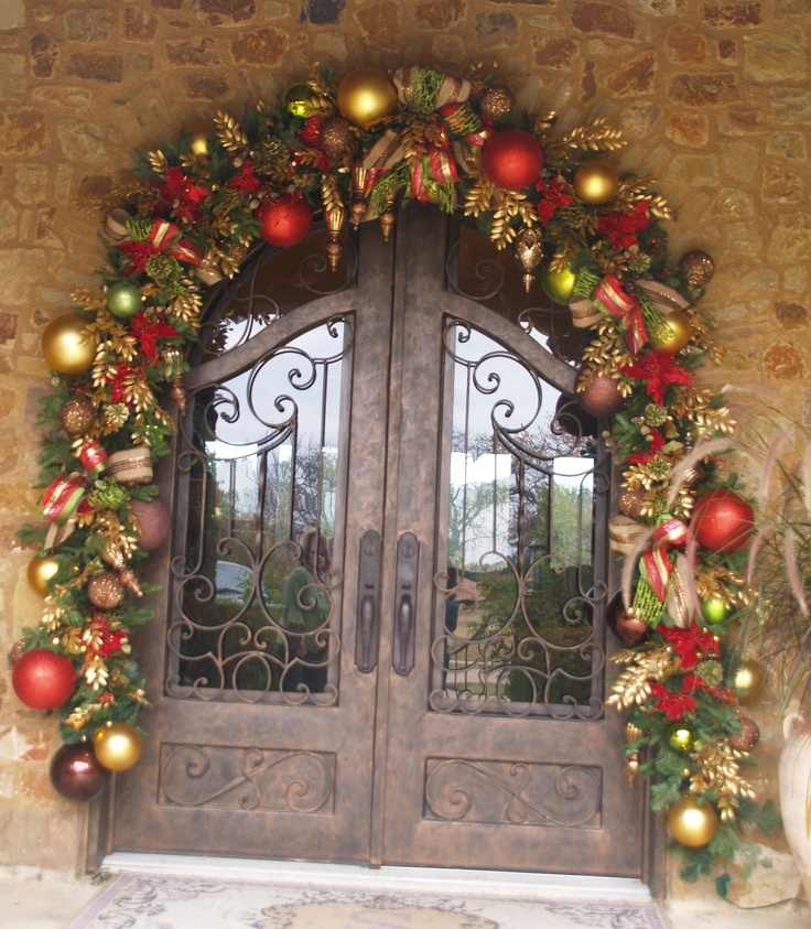 gold, red, green ornaments and striped ribbons and evergreens over the doors to bring a festive feel to the outdoor space