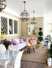 a bright spring porch with lots of greenery, bright throws and blooms feels like the season