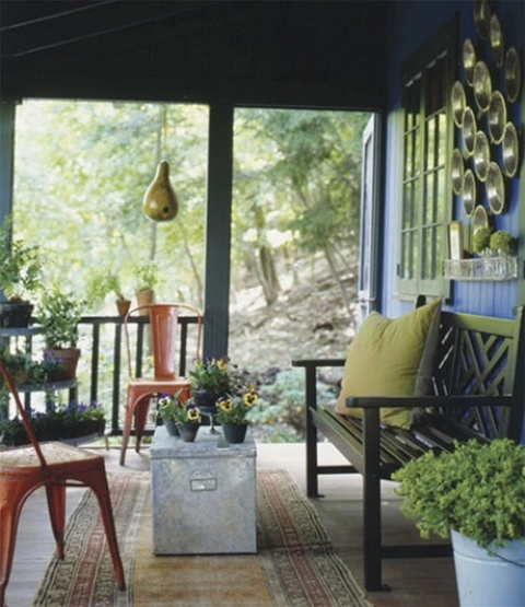 lots of potted flowers and some greenery plus bright pillows for a colorful spring porch