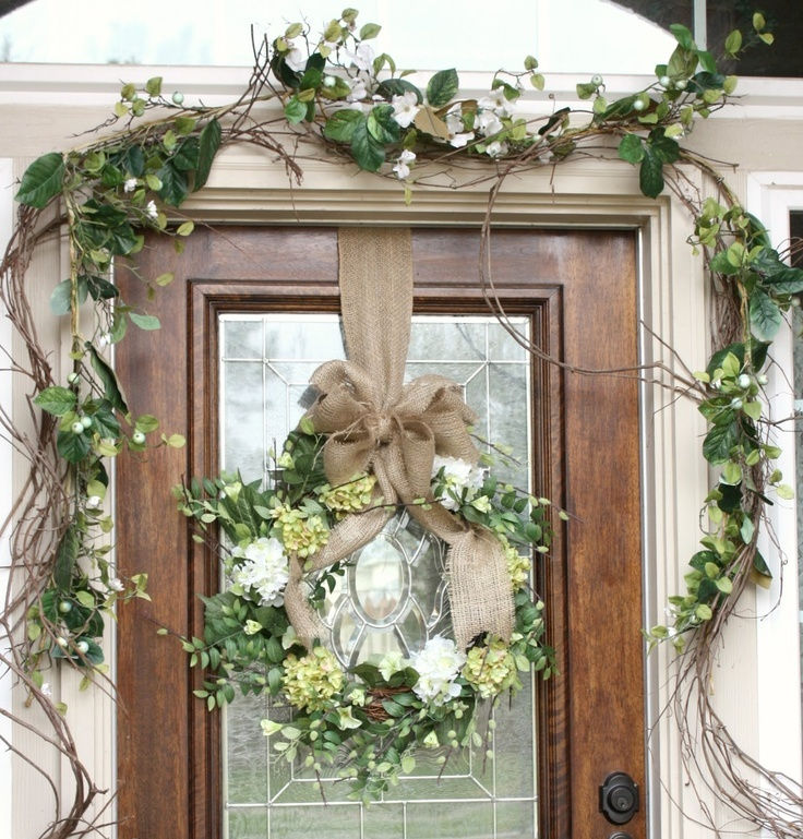 faux greenery, white and green blooms plus vines and a wreath on burlap for a rustic spring porch