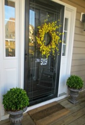 a couple of green topiaries in vintage urns and a bright yellow wreath on the door is a cool idea for spring