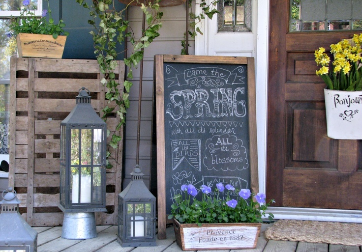 candle lanterns, a chalkboard sign and some bright potted blooms will create a fresh and bold spring feel in the space