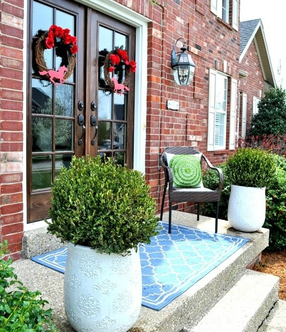 lush greenery in large pots and colorful wreaths on the doors will spruce up your porch for spring