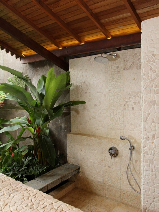 a neutral indoor-outdoor bathroom with stone-inspired tiles, a shower and statement tropical plants