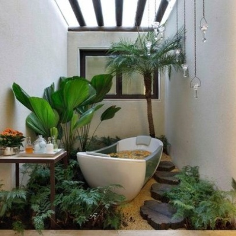 a tropicla bathroom in neutrals, with wooden beams, a tub placed in pebbles, statement plants growing around and pendant lamps