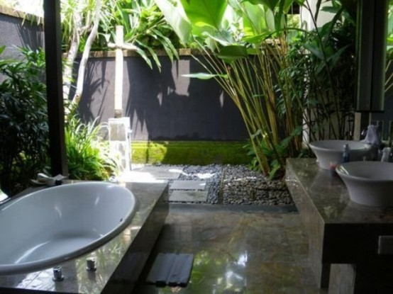 an outdoor-indoor tropical bathroom with pebbles and growing tropical plants and a shower outside, a bathtub inside and sinks on a stone vanity