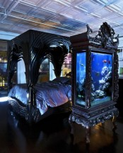 a large aquarium enclosed into a refined and chic black dresser to match the room design