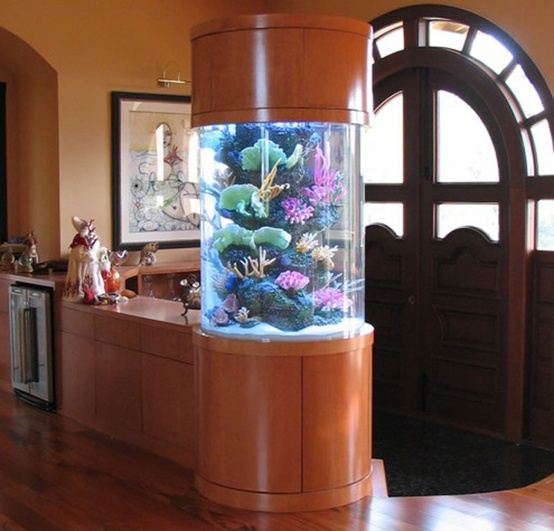 a round aquarium enclosed into rich-stained wood makes a lovely decor feature and separates the entryway from the rest of the house