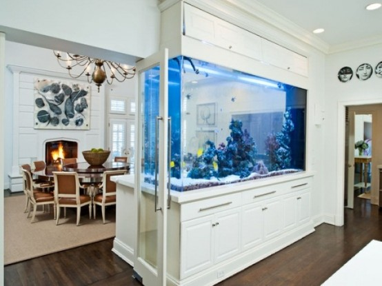 a large aquarium clad with white panels divides the dining and living room and adds to the decor of both spaces