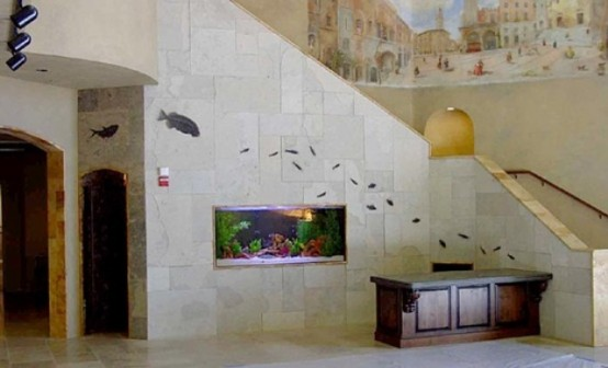 an aquarium built into a stone staircase is a stylish decor feature for this foyer