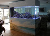 an aquarium with the sea painted on the stand is a gorgeous idea for those who love the sea and sea creatures