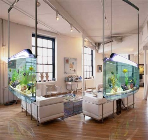 a stylish living room zone in neutrals limited on two sides by hanging aquariums that work as space dividers