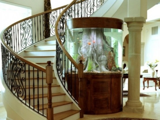 a foyer with an oversized aquarium with rich-stained wood perfectly matches the space and looks very catchy here