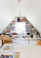a stylish eclectic home office with built-in shelves, a desk, pillows, chairs, a bech and a glass coffee table plus cool ceiling and floor lamps