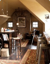 an industrial home office with small windows and a skylight, a dark stained desk, metal and wooden stools, a black leather chair, pendant lamps and printed rugs plus wall sconces