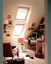 a small attic home office with a skylight, a desk, a chair and some stools, built-in shelves and a cool gallery wall on two walls is cool