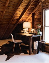 a rustic home office with stained wood walls and a ceiling, a stained desk, a white chair, a table lamp and a large window is a very cool space for working