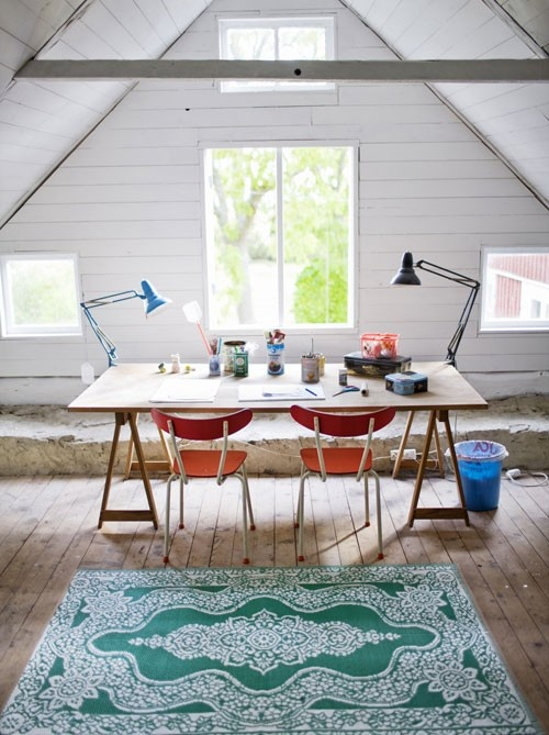 an attic home office with planked walls and a ceiling, a wooden beam and lots of windows, a trestle desk, orange chairs, a printed rug and table lamps