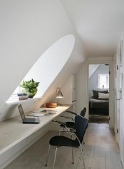 a small white attic home office with an arched window, a long built-in floating desk, a built-in storage cabinet and some artworks on the wall